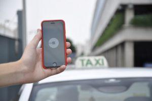 Persona que a través de su móvil pide un coche con Uber